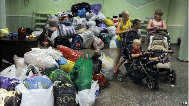 Children stand next to belongings in a hostel for people displaced by fighting in Iloaisk, Ukraine (5 June 2014)