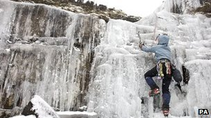 An ice climber at a frozen waterfall in the Brecon Beacons