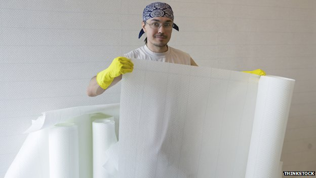 Man holding a roll of wallpaper