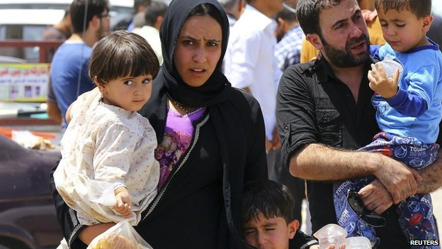 A family fleeing the violence in the Iraqi city of Mosul waits at a checkpoint near Erbil, in Iraq's Kurdistan region, 10 June 2014