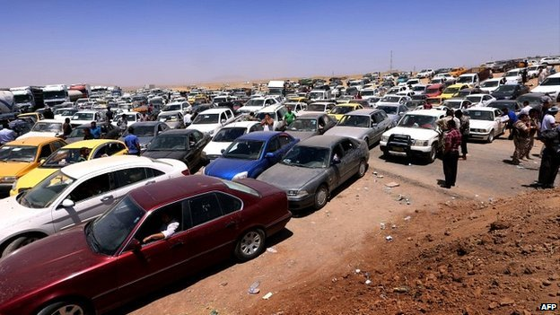 Iraqis fleeing violence in the Nineveh province sit in a traffic jam outside Erbil - 10 June 2014