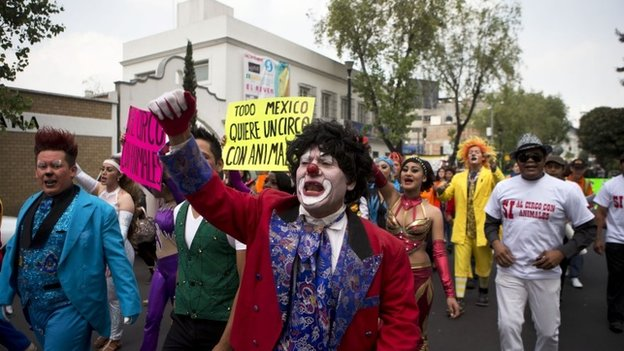 "Clowns and other circus performers march with signs saying ""All of Mexico wants a circus with animals"". 10/06/2014"