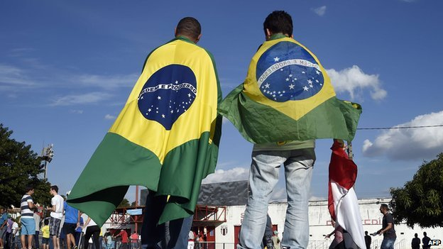 People wearing Brazilian flags arrive at the Santa Cruz Stadium in Ribeirao Prato on 10 June 2014
