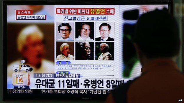 A man watches the TV news program on the reward poster of Yoo Byung-eun at the Seoul Train Station in Seoul, South Korea, on Friday, 23 May, 2014