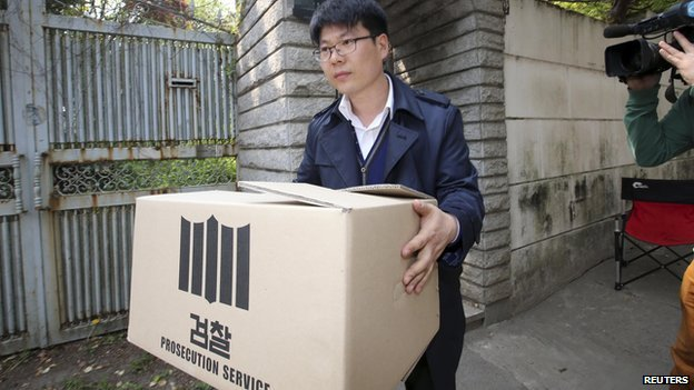 "An official from the Incheon District Prosecutors"" office carries a box during a raid of the home of Yoo Byung-un, in Seoul on 23 April, 2014"
