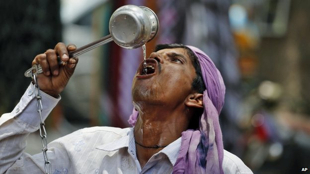 An Indian cycle rickshaw puller drinks water on a hot day in Allahabad, India, Saturday, June 7, 2014. Thousands of people enraged by power cuts during an extreme heat wave have been rioting across northern India, setting electricity substations on fire and taking power company officials hostage, officials said Saturday. (AP Photo/Rajesh Kumar Singh)