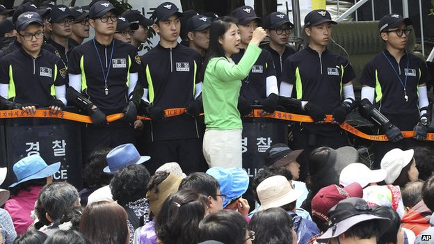 An Evangelical Baptist Church believer shouts slogans against the government as police officers stand guard in font of believers sitting by the main gate of the church in Anseong, South Korea, on Wednesday, 11 June 2014