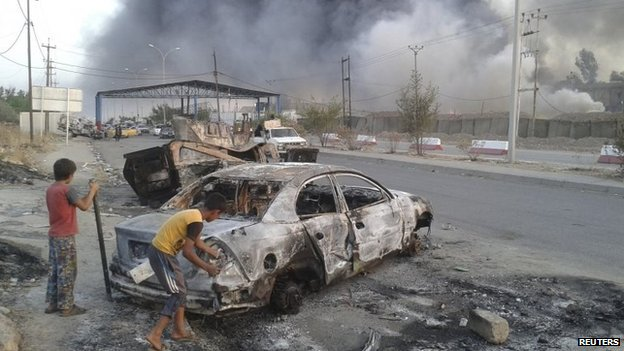 Children stand next to a burnt vehicle during clashes between Iraqi security forces and ISIS
