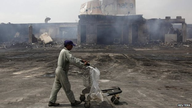 A man pushes a trolley past a damaged building on the tarmac of Jinnah International Airport, a day after Sunday's attack by Taliban militants, in Karachi, 10 June 2014
