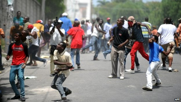 Demonstrators throw stones at the Haitian police during an anti-government protest in Port-au-Prince on 10 June, 2014.
