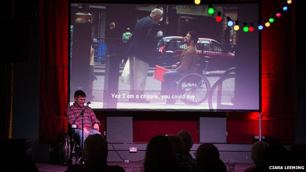 "Laurence Clark on stage in front of a large screen with a picture of him with a man and the subtitle ""Yes I am a cripple, you could say"""