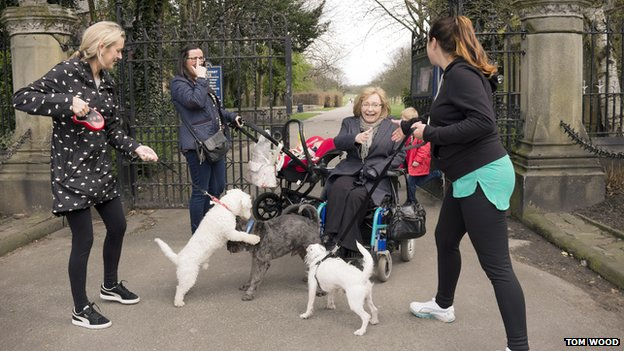 Pam Thomas with three woman with dogs jumping up at her in her wheelchair