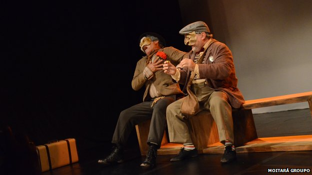 Alexandre Luiz and Silas Queiroz on stage wearing masks and laughing