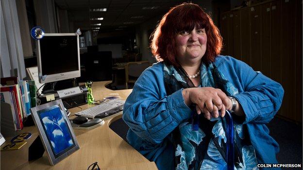 Sarah Bush sitting at a desk holding her stick