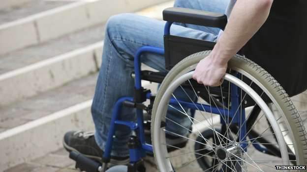 A man in a wheelchair at the base of some stairs