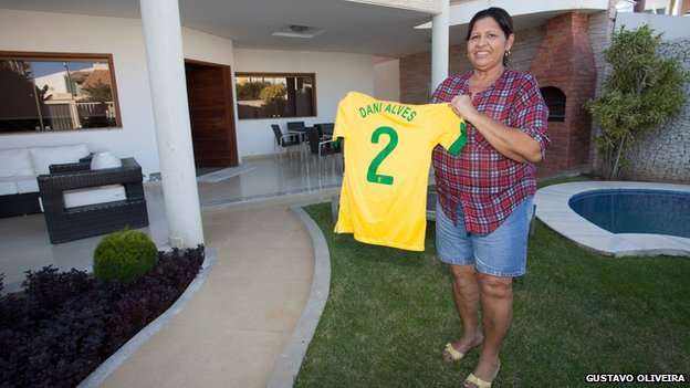 Daniel Alves's mother holds up a jersey with his name