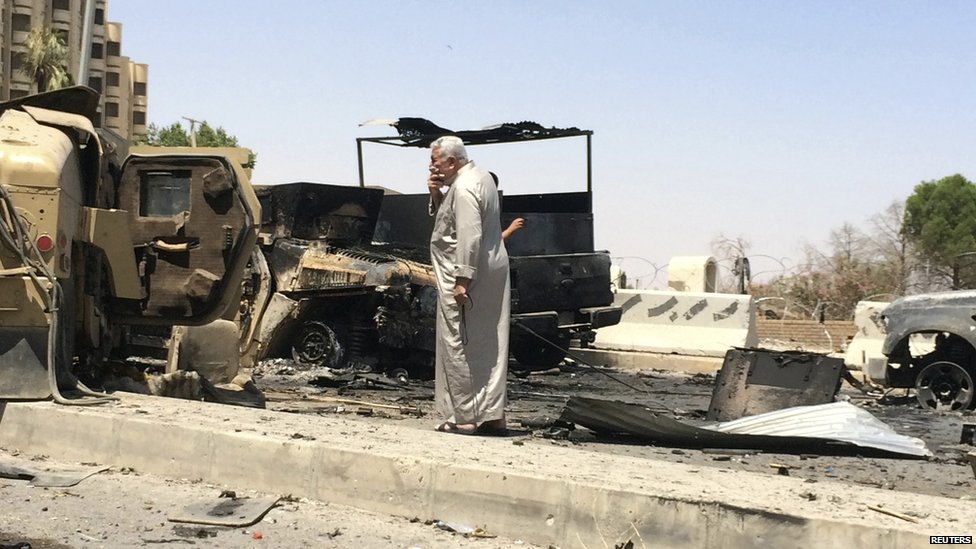 A man looks at burnt vehicles belonging to Iraqi security forces one day after insurgents seized control of the city of Mosul on 11 June 2014.