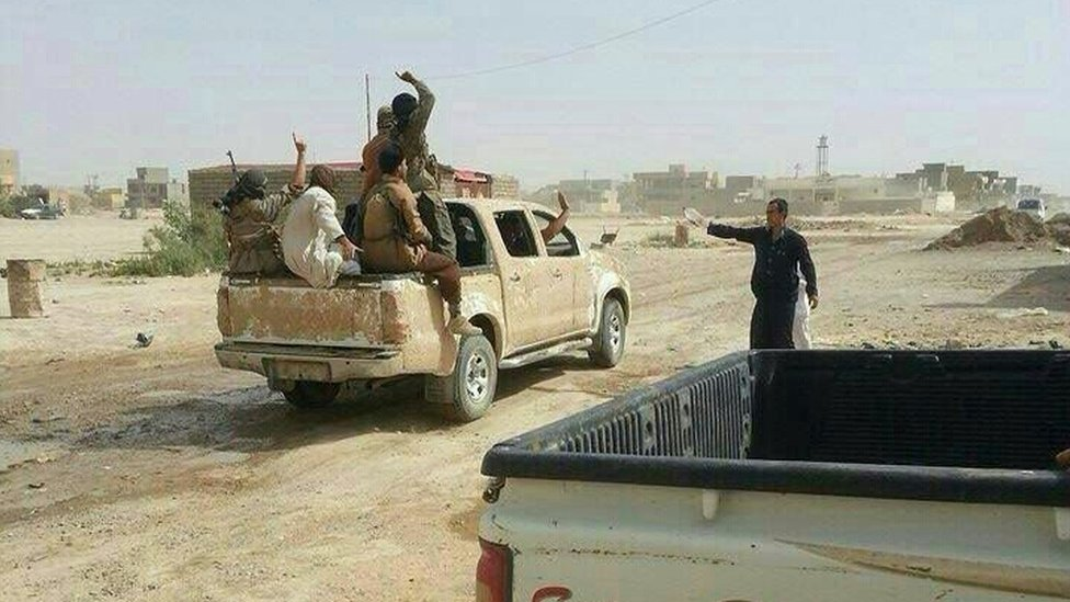Militants gesture as they drive through Tikrit