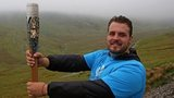 Aled Sion Davies with the Queen's Baton on Snowdon