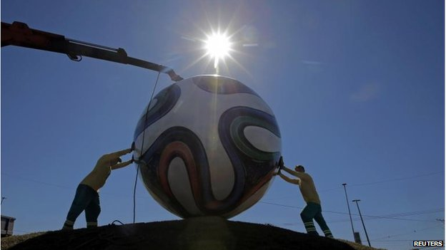 Workers install a giant soccer ball in Cuiaba prior to 2014 World Cup