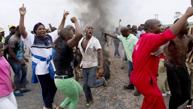 Protesting residents place burning tyres to create a roadblock while marching on the main road leading into the town of Bronkhorstspruit during a protest over poor public service delivery in South Africa on 6 February 2014
