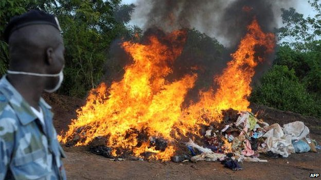 Ivory Coast drug enforcement gendarme watches as the contents of seized bags which reportedly contained more than a tonne of cannabis is incinerated in Bouafle on 26 June 2009