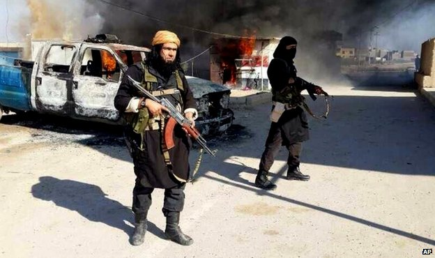 Undated image posted on a militant website in January 2014 shows Islamic State of Iraq and the Levant fighters next to a burning vehicle in Iraq's Anbar Province