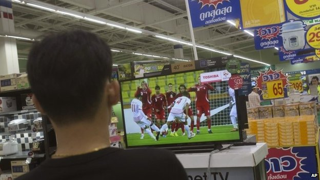 A Thai shopper watches a soccer match on a flat-panel television at a shopping mall in Bangkok, Thailand Wednesday, June 11