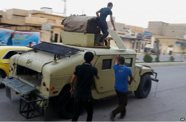 Teenagers ride a captured Iraqi army vehicle in Tikrit, 11 June