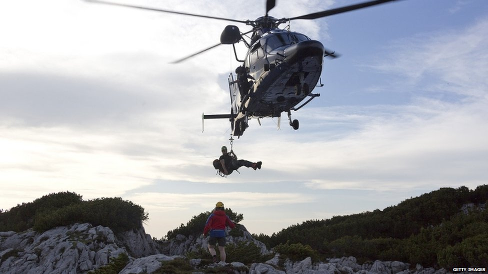 A helicopter delivers rescuers near the entrance to the the Riesending cave