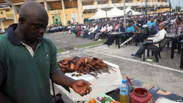 A man prepares barbecue popularly known as Suya for fans watching Nigeria's match against Ethiopia at a public viewing centre in Lagos - 29 January 2013