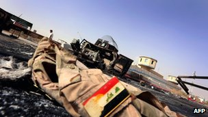 An Iraqi army uniform lies on the ground in front of of a burnt Iraqi army vehicle near Mosul