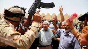 Iraqi men and a soldier chant anti-ISIS slogans in Baghdad. Photo: 12 June 2014