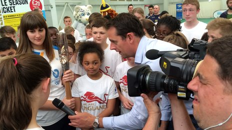 BBC reporter Ben Moore interviews school children about the Queen's baton