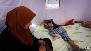 An Iraqi family rests in a tent at a temporary camp near Arbil, 12 June 2014
