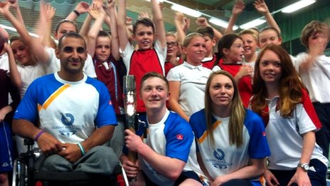 Ali Jawad and Nile Wilson hold the Queen's Baton in the tennis centre in Leeds