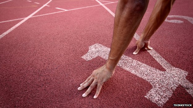 An athlete crouches into a pose in lane one of a running track