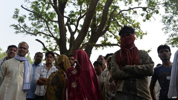 Mothers of gang-rape victims (C, shawls covering their faces) and villagers stand in front of the mango tree where the girls were hanged in Katra Shahadatgunj in Badaun district (31 May 2014)