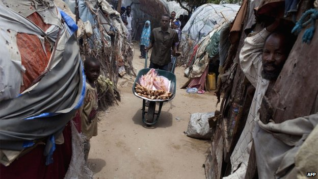 A man sells loafs of bread from a wheelbarrow in a displacement camp in Mogadishu