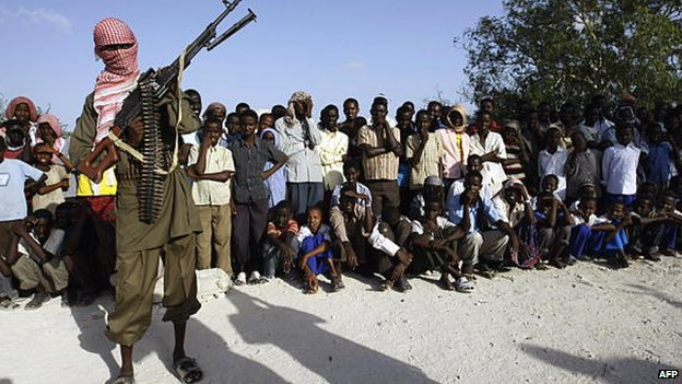 A hooded Somali Islamist fighter stands guard over a crowd that gathered to watch the public flogging of teenaged boys convicted of raping a minor in Mogadishu, Somalia - 2009