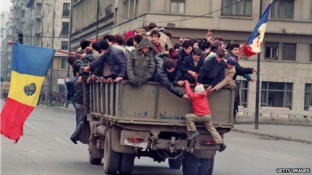 Romanian civilians cross Bucharest on a truck waving flags where the communist symbol has been cut off,  on December 24, 1989
