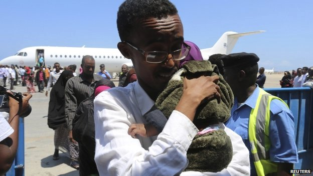 A Somali man and his child deported from Kenya arrive at the airport in Somalia's capital, Mogadishu, 9 April 2014