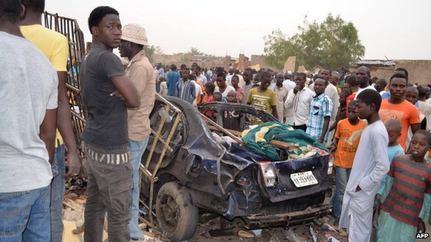 People look at the wreckage of a car on 2 March  2014, after two deadly explosions in a crowded neighbourhood of Maiduguri, Nigeria