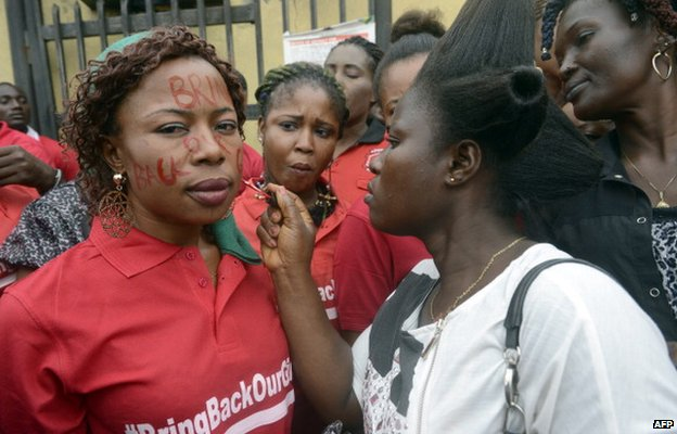 "A woman writes the slogan ""Bring Back Our Girls"" on the face of another as they prepare to march in Lagos, Nigeria, on 29 May 2014"