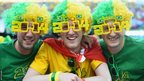 Fans in 2014 shaped glasses pose in the stands at the Arena de Sao Paulo ahead of the World Cup opener between Brazil and Croatia