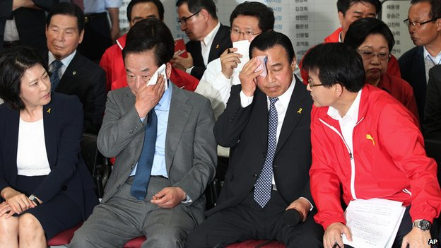 Lee Wan-goo, Chairman of the Party's campaign, wipes the sweat off his face as members watch a television program broadcasting the election exit polls in Seoul, South Korea, on Wednesday, 4 June, 2014