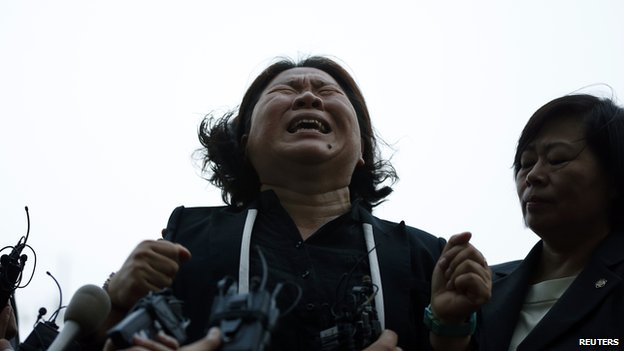 The mother of a victim onboard sunken ferry cries as she speaks to the media in front of a building in which crew members are detained, after attending a hearing at the local court in Gwangju on 10 June, 2014
