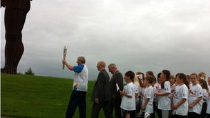 Brendan Foster with the baton at the Angel of the North