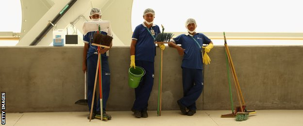 Workers take a break as they prepare the stadium at the Arena Amazonia in Manaus ahead of England's first game.