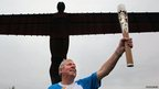 Baton-bearer Brendan Foster holding the Queen's Baton at the Angel of the North, Newcastle